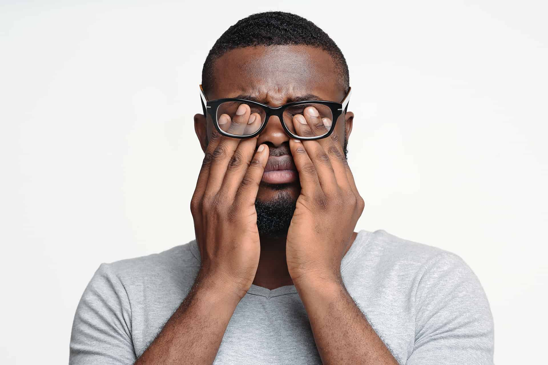 Afro guy in glasses rubbing his eyes